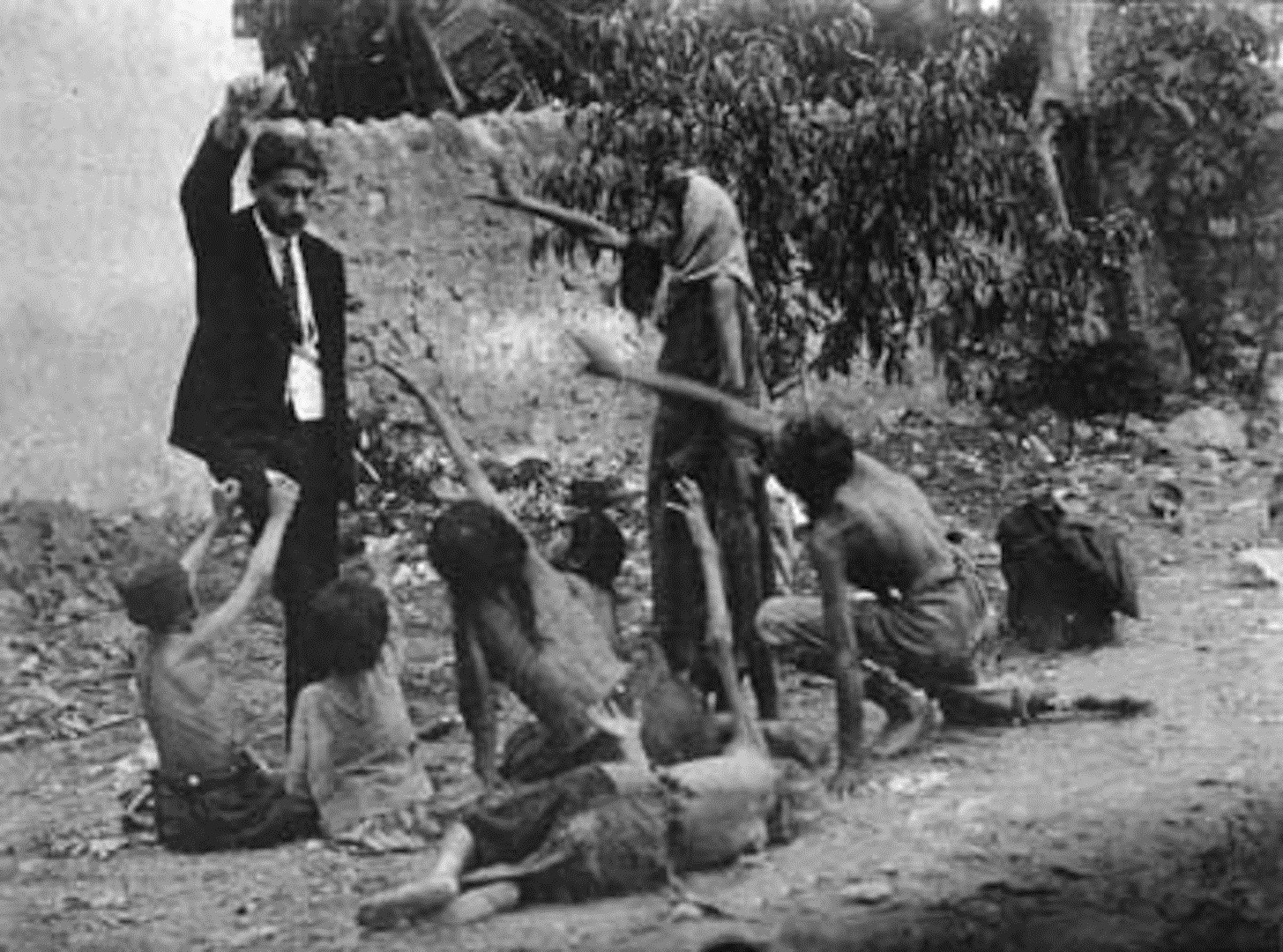 Turkish official teasing starved Armenian children with food during the Armenian Genocide (1915)
